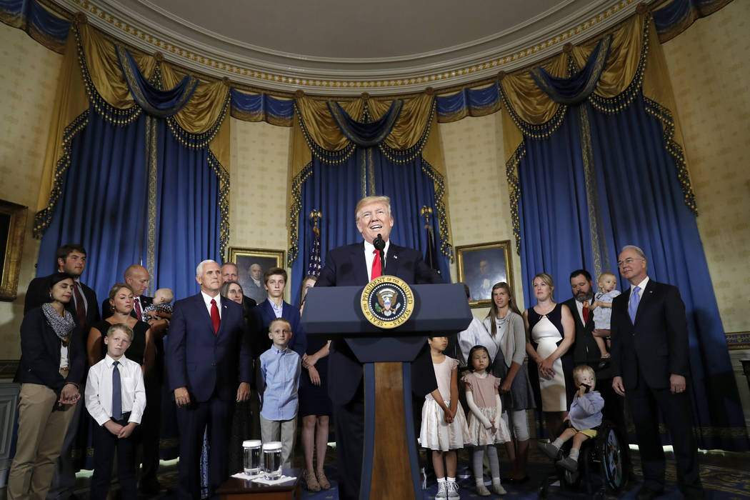 President Donald Trump, accompanied by Vice President Mike Pence, Health and Human Services Secretary Tom Price, and others, speaks about healthcare, Monday, July 24, 2017, in the Blue Room of the ...