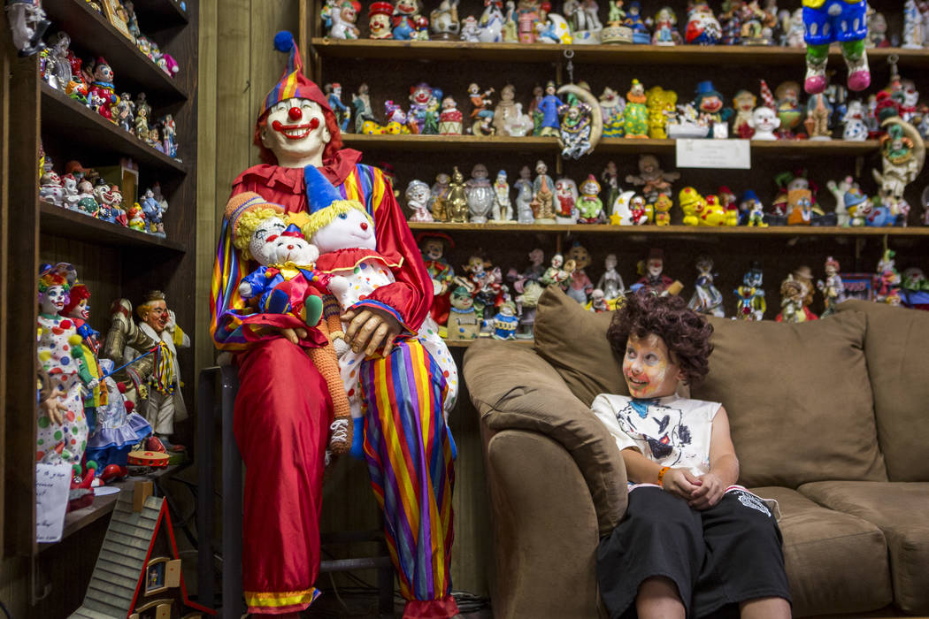 """Kai James, 9, glances over at the life-size clown known as """"Mr. Creepy"""" in the lobby of the Clown Motel in Tonopah on Tuesday, July 25, 2017. James came with his brother and moth ..."""