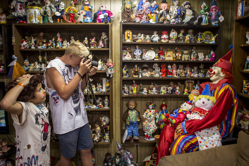 """Caden James, 15, takes a photo of the clown known as """"Mr. Creepy"""" as his brother Kai, 9, watches in the lobby of the Clown Motel in Tonopah on Tuesday, July 25, 2017. The Las Veg ..."""