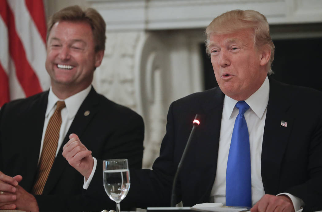 President Donald Trump gestures towards Sen. Dean Heller, R-Nev. while speaking during a luncheon GOP leadership, Wednesday, July 19, 2017, in the State Dinning Room of the White House in Washingt ...