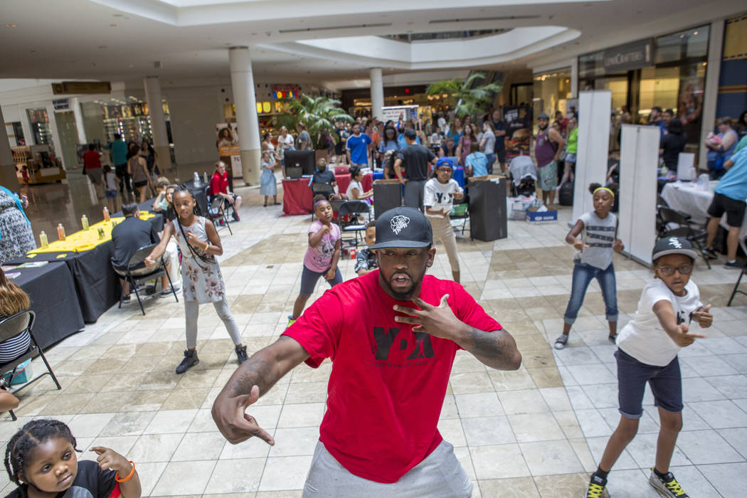 Dhon Blackwell, an instructor with Youth Dance Academy, shows kids some hip-hop moves during a Supply a Teacher event at the Galleria at Sunset Mall in Henderson on Saturday, July 29, 2017.  Patri ...