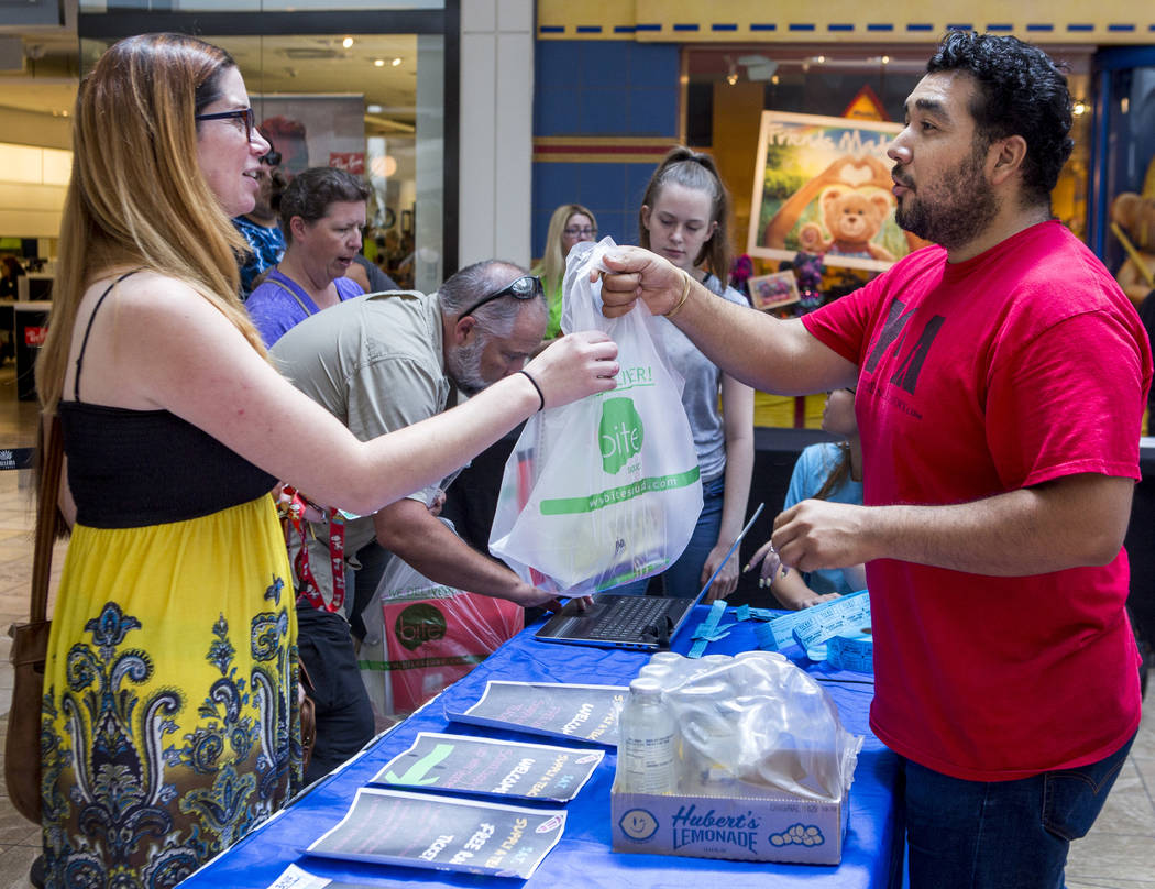 Angel Escamilla, a partner with Live to Give, hands teacher Natalia Borquez her school supplies during a Supply a Teacher event at the Galleria at Sunset Mall in Henderson on Saturday, July 29, 20 ...