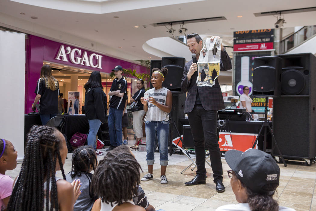 Magician Jason Andrews reveals that Liannah Wallace, 10, was holding the 4 of hearts card based on his newspaper cutting during a Supply a Teacher event at the Galleria at Sunset Mall in Henderson ...