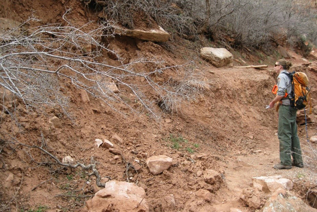 An employee at Zion National Park examines a section of the Middle Emerald Pools Trail destroyed by a landslide in December 2010. (National Park Service)
