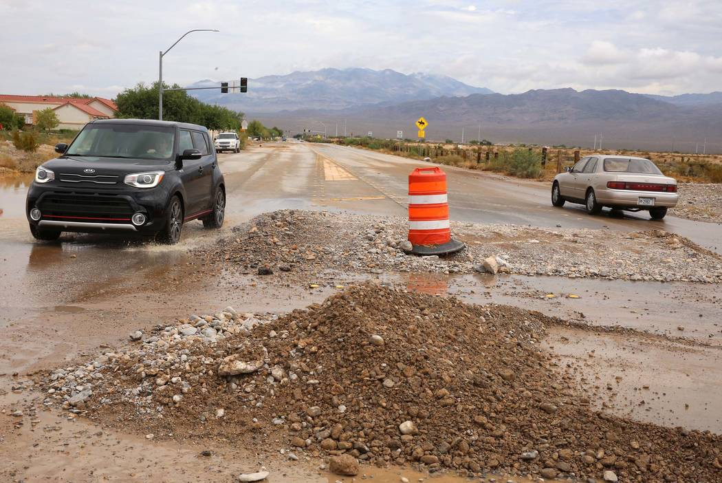Motorists drive past flood debris left behind at the intersection of Durango Drive and Brent Lane on Tuesday, July 25, 2017, in Las Vegas. (Bizuayehu Tesfaye/Las Vegas Review-Journal) @bizutesfaye