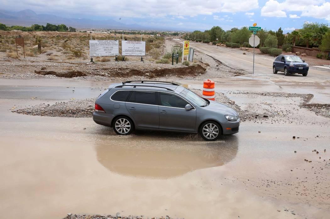Motorists navigate through flooded street at the intersection of Durango Drive and Brent Lane on Tuesday, July 25, 2017, in Las Vegas. (Bizuayehu Tesfaye/Las Vegas Review-Journal) @bizutesfaye