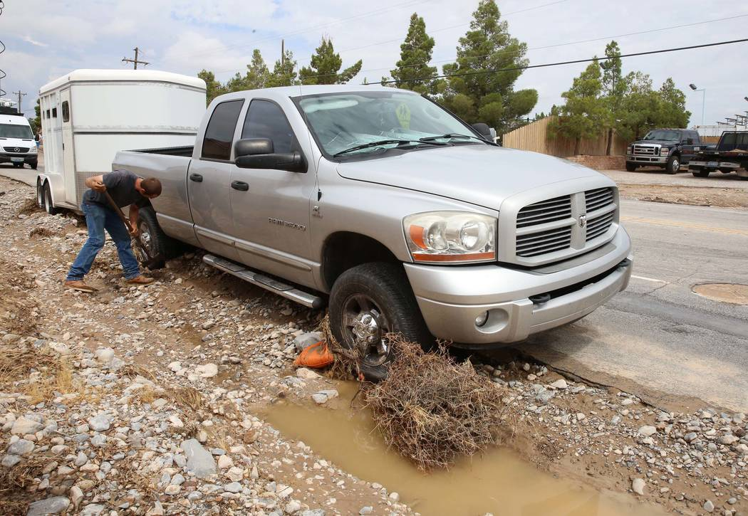 Clinton Jacob tries to free his truck and horse trailer from flood debris outside his home on Brent Lane on Tuesday, July 25, 2017, in Las Vegas. (Bizuayehu Tesfaye/Las Vegas Review-Journal) @bizu ...