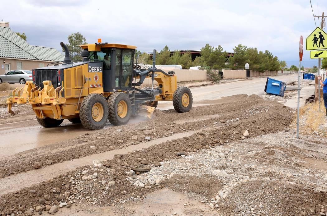 A clean up crew remove flood debris from Brent Lane on Tuesday, July 25, 2017, in Las Vegas. (Bizuayehu Tesfaye/Las Vegas Review-Journal) @bizutesfaye