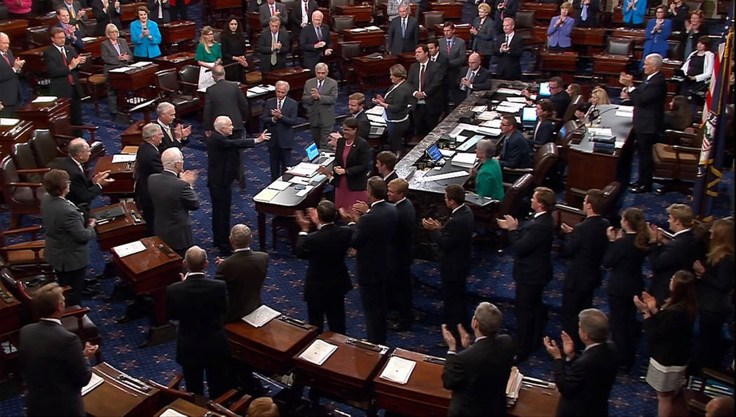 A still image from video shows U.S. Senator John McCain (R-AZ), who had been recuperating in Arizona after being diagnosed with brain cancer, acknowledging applause as he arrives on the floor of t ...