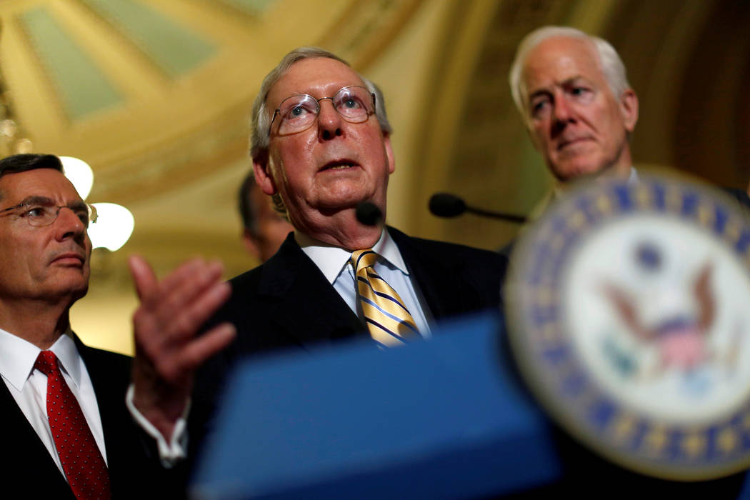 Senate Majority Leader Mitch McConnell, accompanied by Senator John Cornyn (R-TX) and Senator John Barrasso (R-WY), speaks with reporters following the successful vote to open debate on a health c ...
