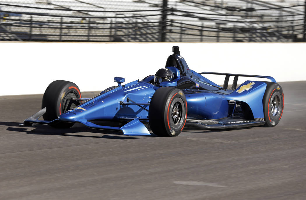 Two-time Indianapolis 500 winner Juan Pablo Montoya drives down the main strait in a newly-designed IndyCar at the Indianapolis Motor Speedway, Tuesday, July 25, 2017 in Indianapolis.  (AP Photo/M ...