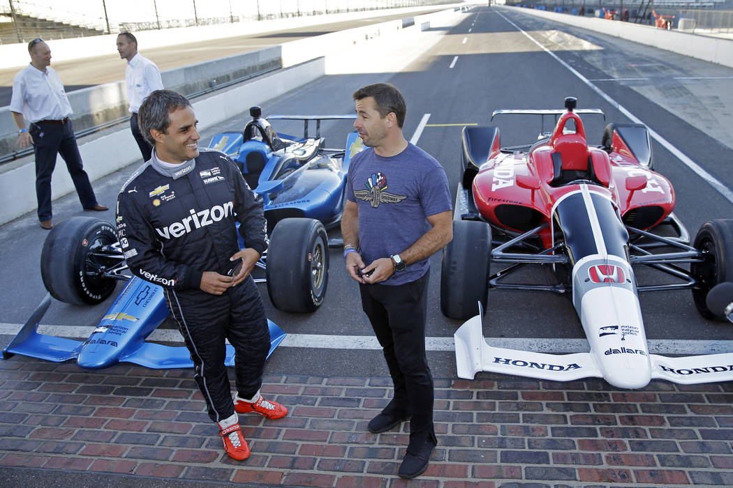 Two-time Indianapolis 500 winner Juan Pablo Montoya, left, and Spanish driver Oriol Servia talk in front of the newly-designed IndyCars at the Indianapolis Motor Speedway, Tuesday, July 25, 2017,  ...