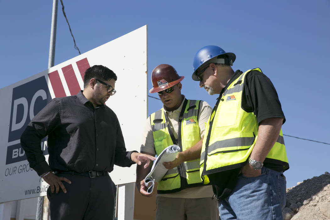 Akashi Bhatti (left), Construction Superintendent Mike Stephenson (center), and Construction Superintendent Bruce Konold (right) look over construction plans for the future site of an Arco gas sta ...