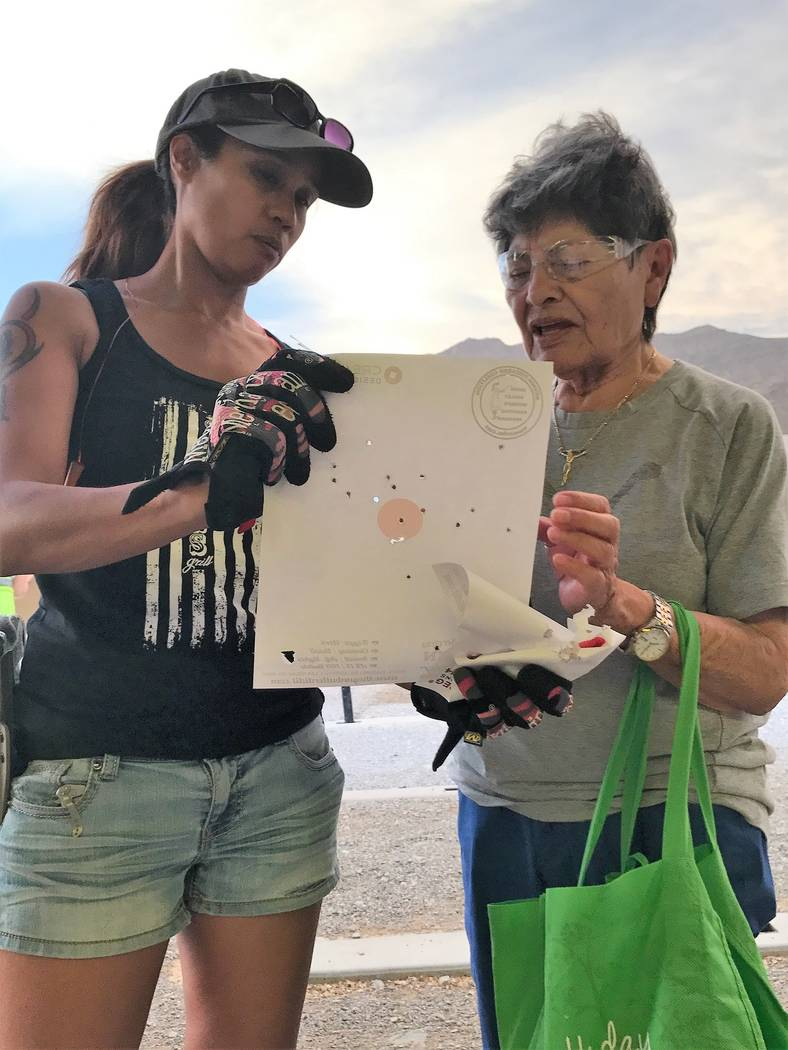 Soledad Garcia shows Jeannette Morgan, coordinator of the Annie Oakley Women's Shooting Program, her bullseyes. Garcia hopes to one day hit only bullseyes. (Doug Nielsen)