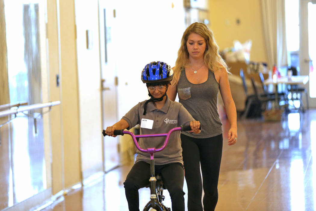 Mira Modha rides a bike under the supervision of volunteer Paige LeBeau at a bicycle camp for adults and children with disabilities on Thursday, July 27, 2017, at Opportunity Village's Engelstad C ...