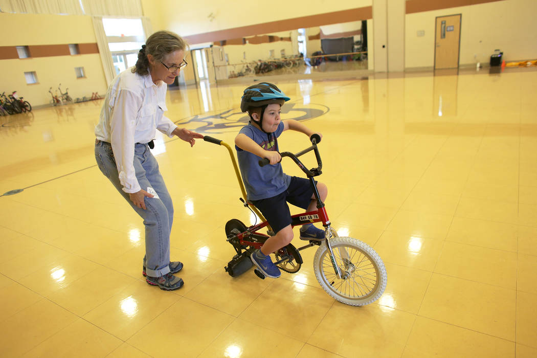 Cooper Adams, 7, rides a bike under the supervision of Kacy Curry at a bicycle camp for adults and children with disabilities on Thursday, July 27, 2017, at Opportunity Village's Engelstad Campus. ...
