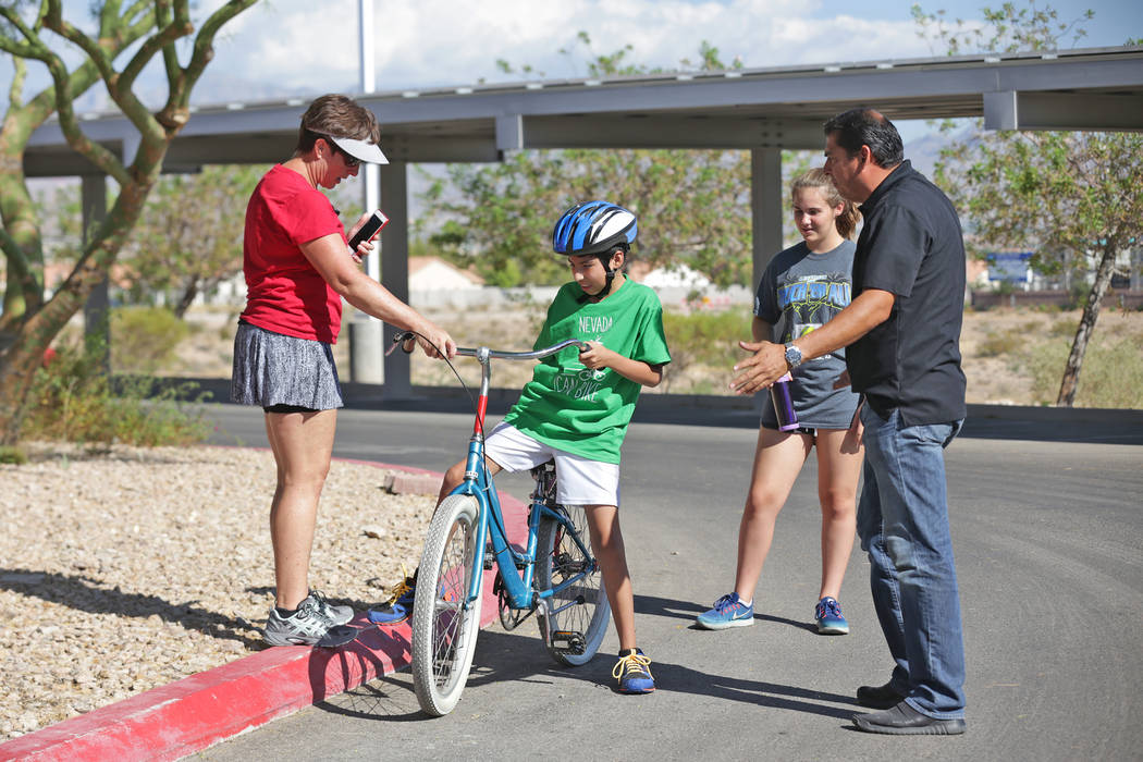 Allesandro Briceno, 10, center, gets help from Diana Ruvetti, from left, volunteer Chloe Adams, 17, and his father Marco Briceno at a bicycle camp for adults and children with disabilities on Thur ...