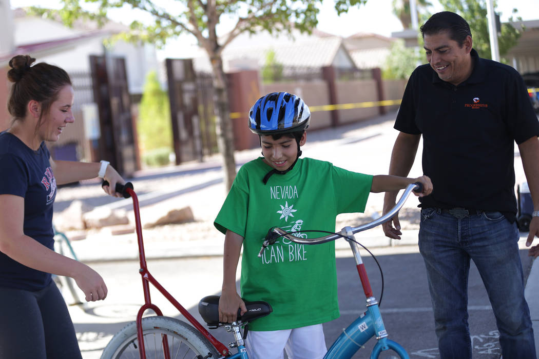 Volunteer Jill Rovetti, 17, from left, helps Alessandro Briceno, 10, push off on a bike ride as Alessandro's father Marco Briceno watches at a bicycle camp for adults and children with disabilitie ...