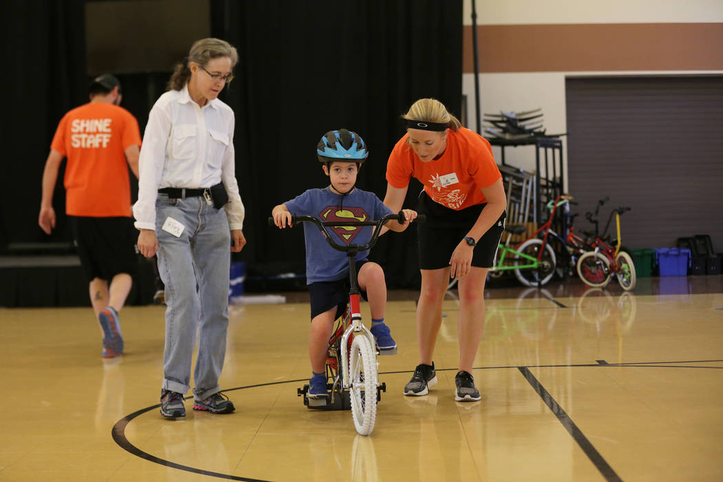 Volunteers Kacy Curry, left, and Gabey Davis help Cooper Adams, 7, learn to ride a bike at a bicycle camp for adults and children with disabilities on Thursday, July 27, 2017, at Opportunity Villa ...