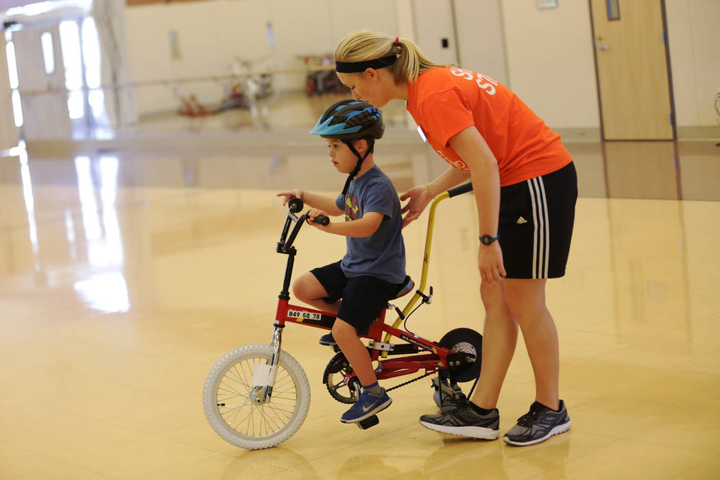Volunteer Gabey Davis helps Cooper Adams, 7, learn to ride a bike at a bicycle camp for adults and children with disabilities on Thursday, July 27, 2017, at Opportunity Village's Engelstad Campus. ...