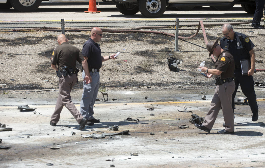Police sort through the debris from the plane crash that killed four people in the median of I-15 near Riverdale, Utah, Wednesday, July 26, 2017. The crash closed the freeway to northbound traffic ...