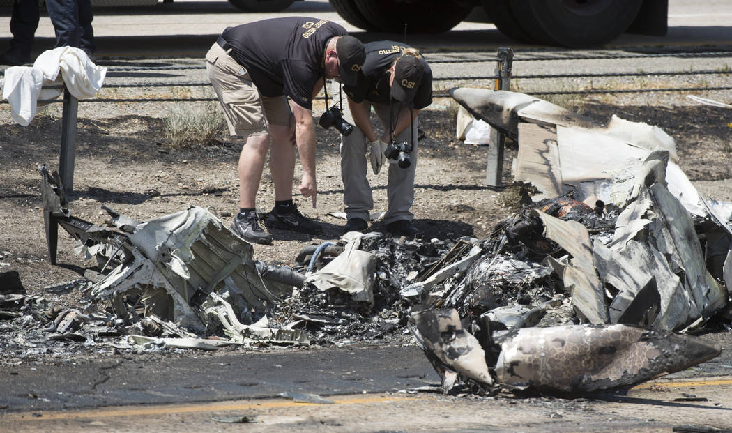 CSI investigators sort through the debris from the plane crash that killed four people in the median of I-15 near Riverdale, Utah,  Wednesday, July 26, 2017. The crash closed the freeway to northb ...