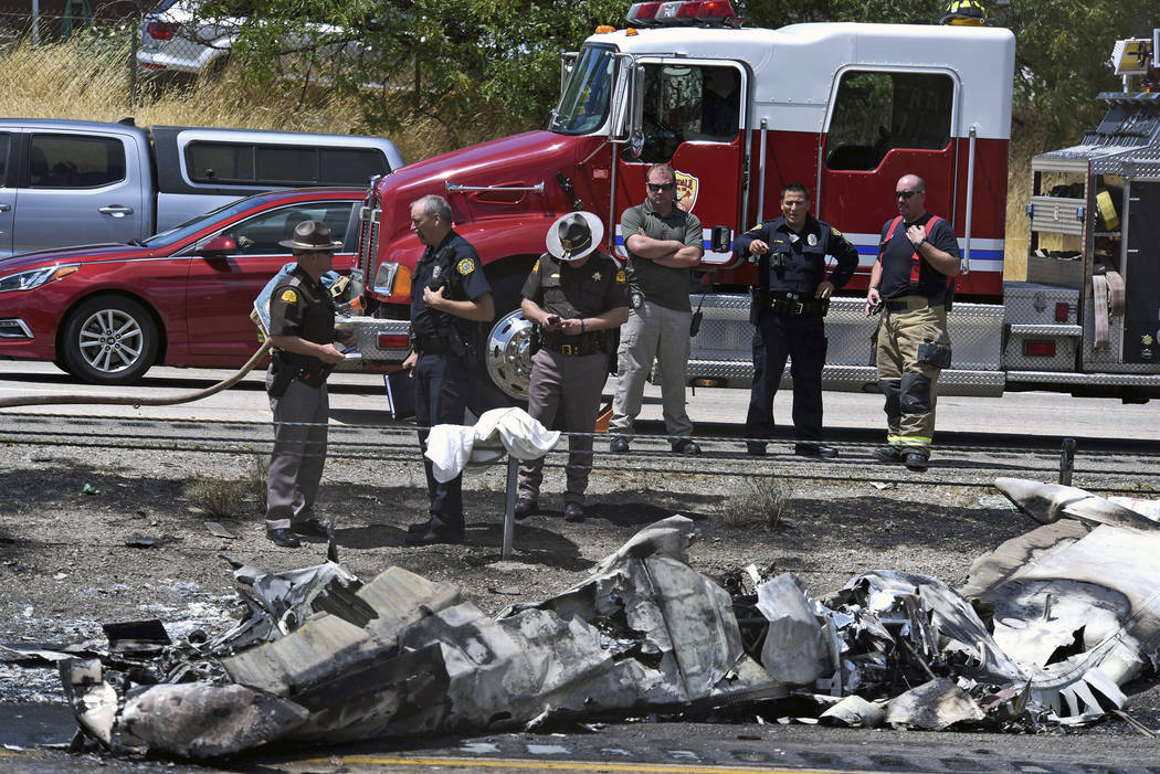 Investigators look over wreckage of a small plane that crashed along Interstate 15 Wednesday, July 26, 2017, near Riverdale, Utah. Authorities say four people died when a small plane crashed on a  ...