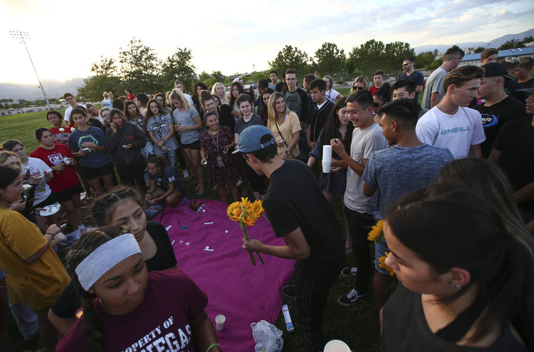People lay down flowers during a vigil for Haylei Hughes, a former Cimarron-Memorial student-athlete, who died in a hiking accident in Wash., at Kellogg Zaher Sports Complex in Las Vegas on Thursd ...