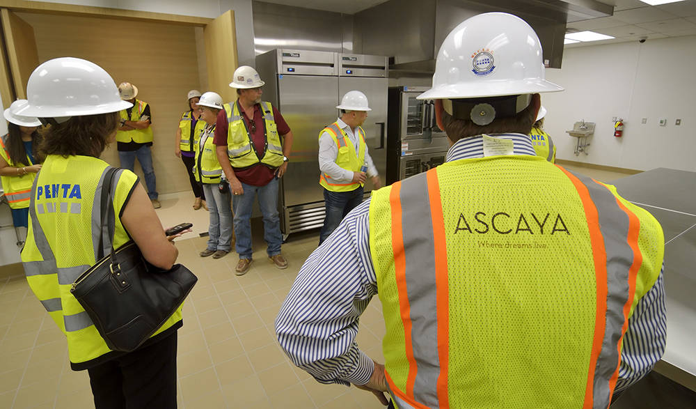 The Ascaya crew look over the  Wolfgang Puck-designed kitchen. (Bill Hughes Real Estate Millions)