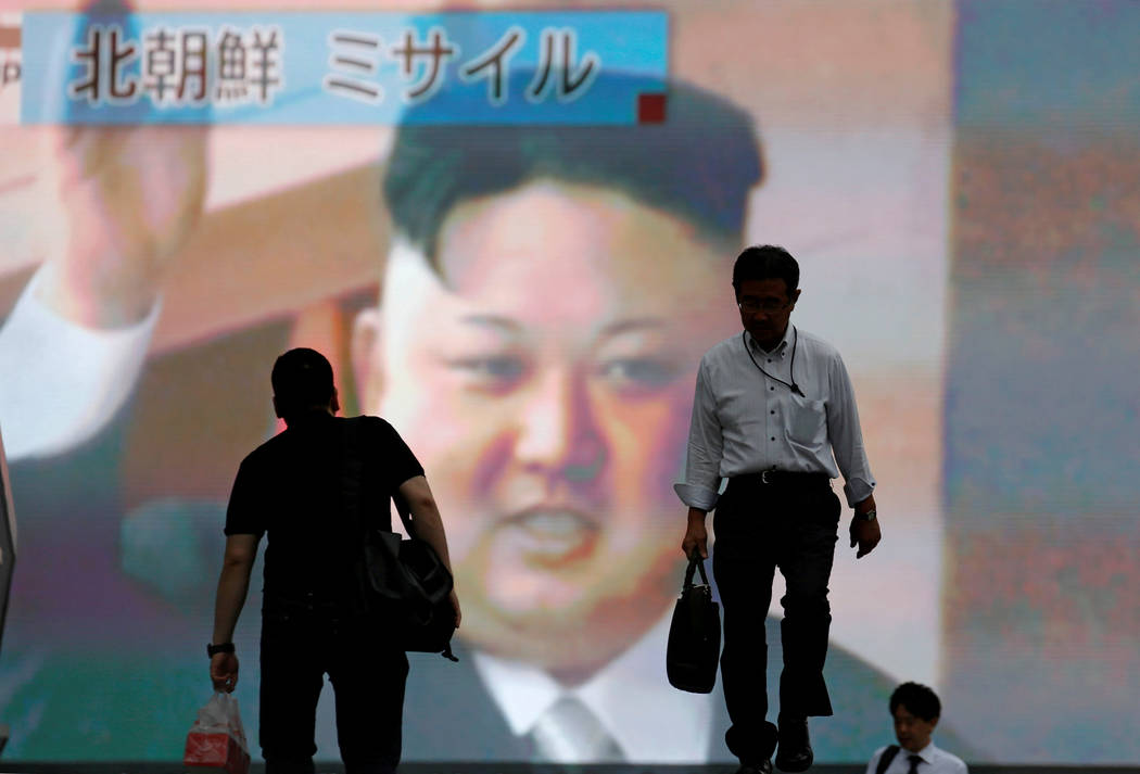 Men walk past a street monitor showing news of North Korea firing a ballistic missile, in Tokyo, Japan, July 4, 2017. Toru Hanai/Reuters