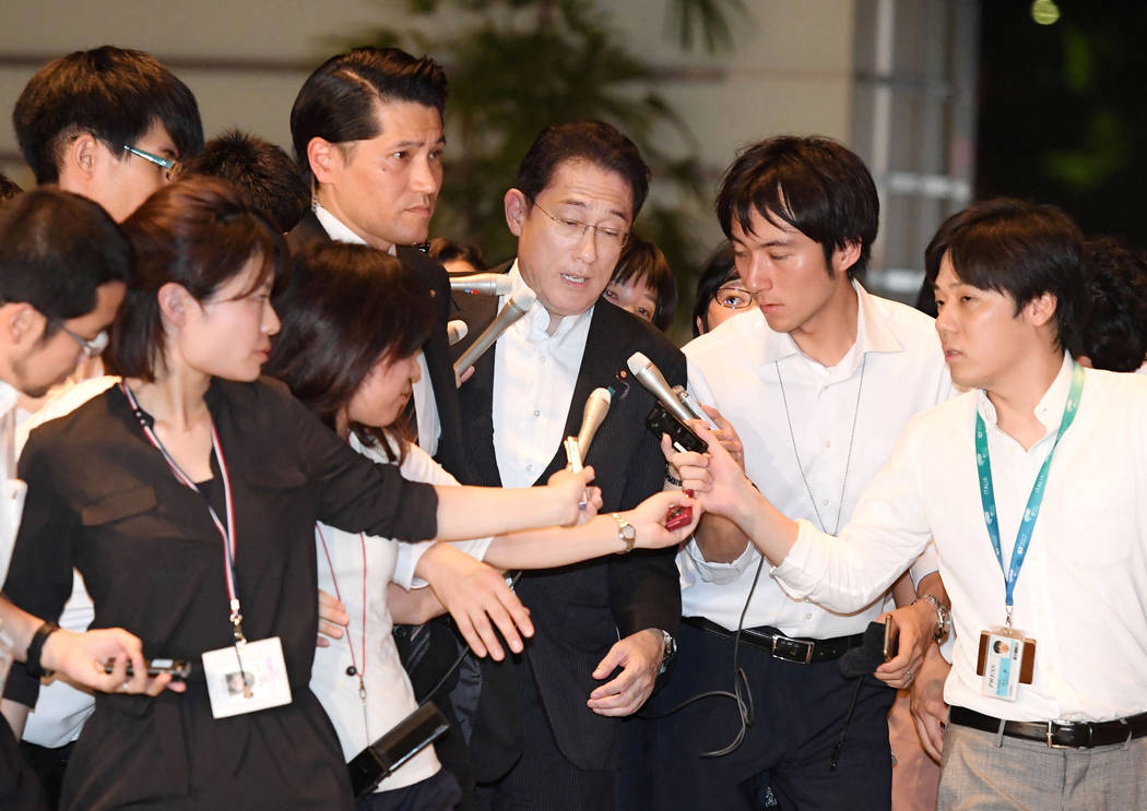 Japan's Foreign Minister Fumio Kishida, center, who is also currently taking role as defense minister, is surrounded by reporters upon his arrival at prime minister's house after reports on North  ...