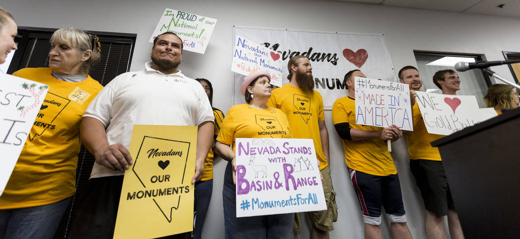People hold signs during a news conference about Secretary Zinke's shortened visit to Nevada at a Battle Born Progress office in Las Vegas, Monday, July 31, 2017.  Zinke's shortened visit was bemo ...