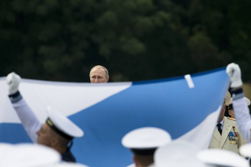 Russian President Vladimir Putin, center, watches as sailors carry a Russian National Navy flag in a military parade during the Navy Day celebration in St. Petersburg, Russia, on Sunday, July 30,  ...