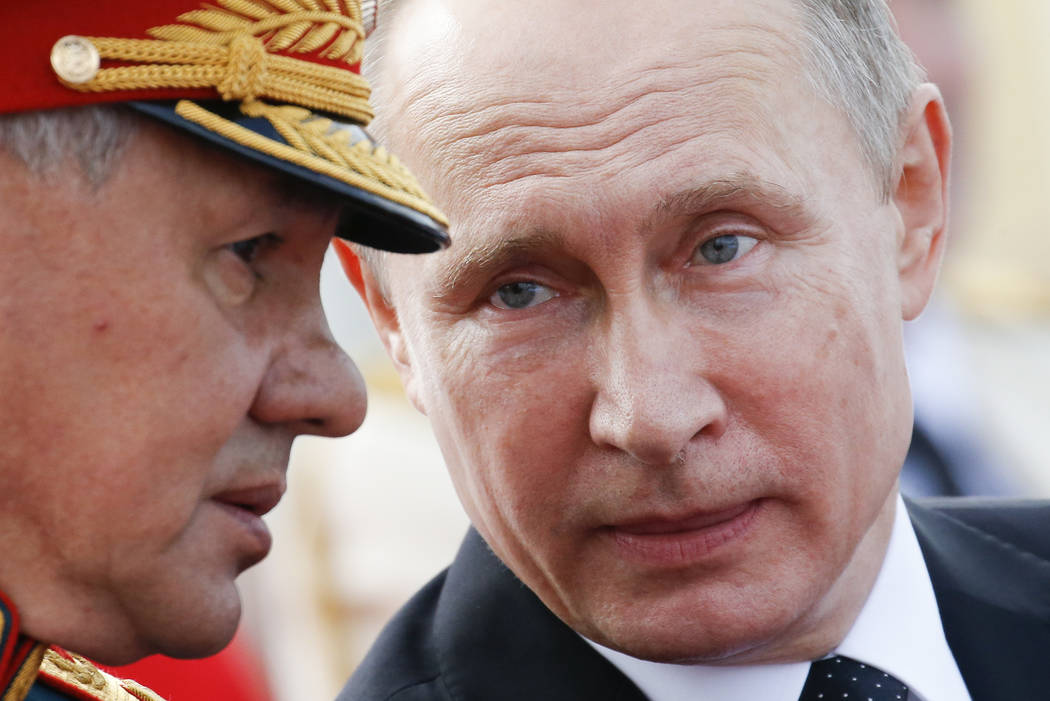 Russian President Vladimir Putin chats with Defence Minister Sergei Shoigu as they attend the military parade during the Navy Day celebration in St.Petersburg, Russia, on Sunday, July 30, 2017. (A ...