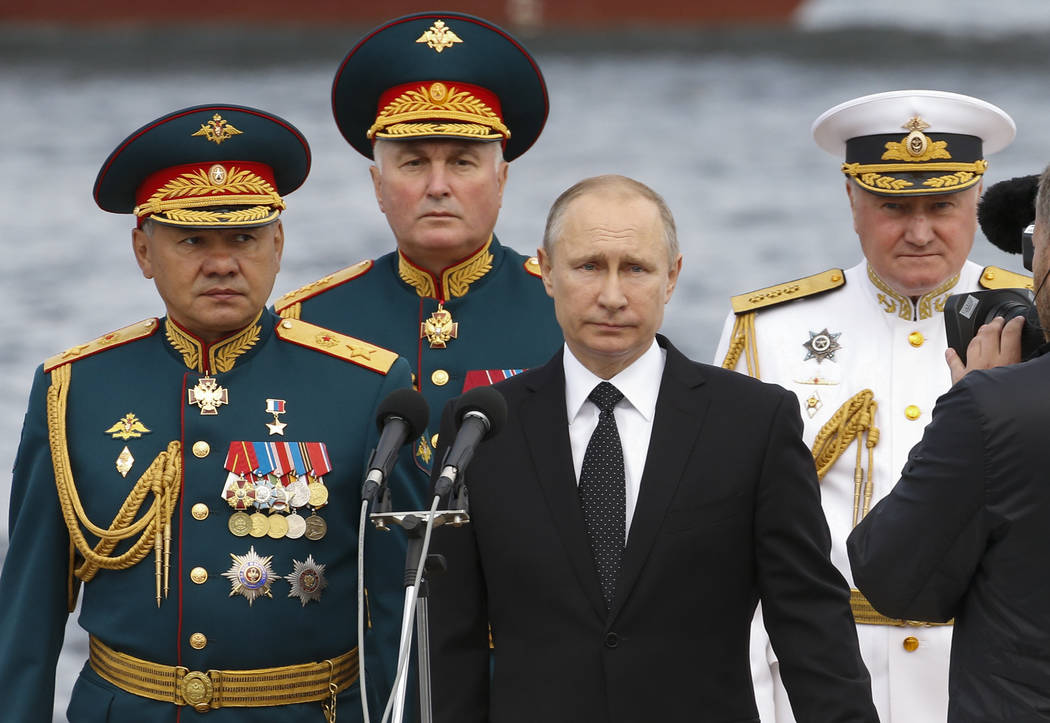 Russian President Vladimir Putin, center, Defence Minister Sergei Shoigu, left, Commander-in-Chief of the Russian Navy Vladimir Korolev, right, and Commander of Western military district Andrei Ka ...