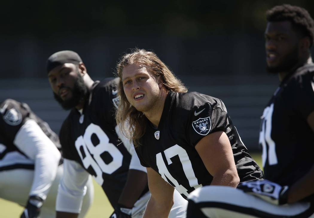 The Oakland Raiders defensive end/linebacker James Cowser, center, stretches during the second day of teams practice at Raiders Napa Valley training complex in Napa., Calif., on Sunday, July 30, 2 ...
