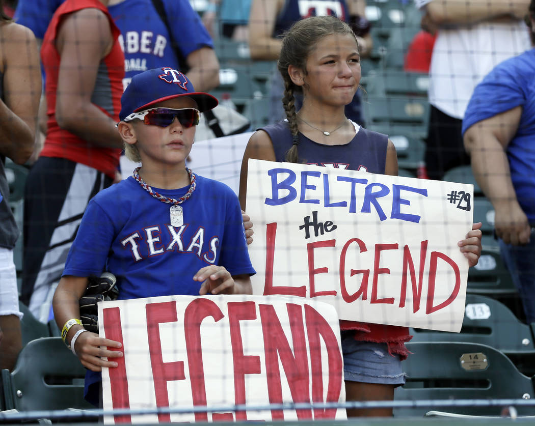 Young fans hold signs as Texas Rangers' Adrian Beltre gives on on field interview after their 10-6 loss to the Baltimore Orioles in a baseball game, Sunday, July 30, 2017, in Arlington, Texas. Bel ...