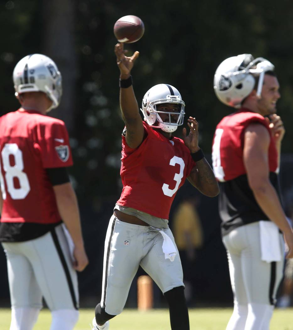 The Oakland Raiders back up quarterback Ej Manuel (3) throws a pass between quarterback Derek Carr, right, and backup quarterback Connor Cook (18) during the second day of teams practice at Raider ...