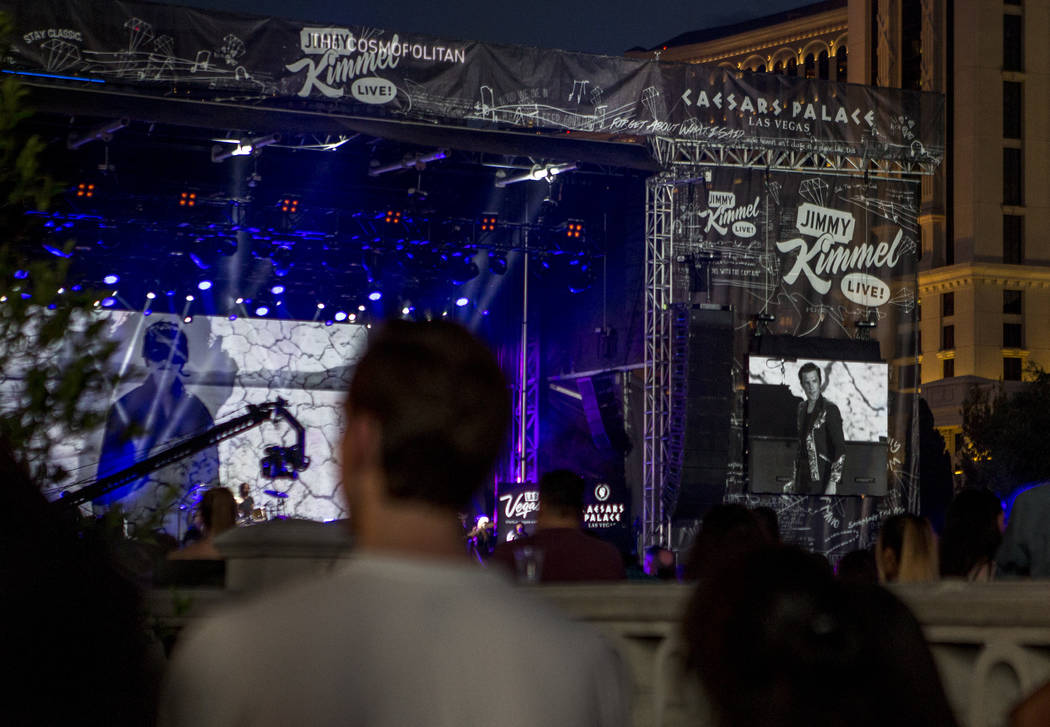 Brandon Flowers of The Killers appears on screens as fans watch from Las Vegas Boulevard as the band performs a pop-up concert to air on Jimmy Kimmel Live! outside of Caesars Palace on Monday, Jul ...