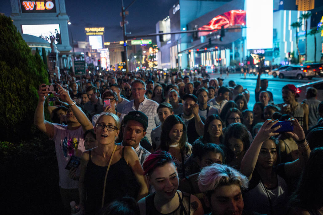 The Killers fans crowd onto the sidewalk of Las Vegas Boulevard near Caesars Palace to listen to the band perform a pop-up concert to air on Jimmy Kimmel Live! outside of Caesars Palace on Monday, ...