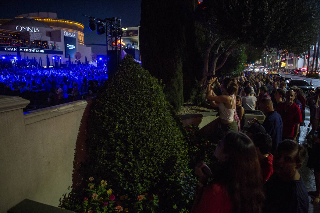 Fans crowd onto the sidewalk of Las Vegas Boulevard near Caesars Palace to listen to The Killers perform a pop-up concert to air on Jimmy Kimmel Live! outside of Caesars Palace on Monday, July 31, ...