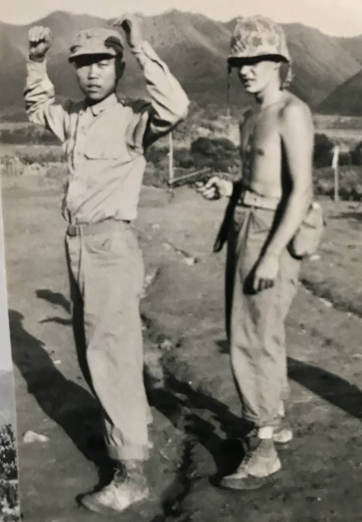 Marine Pfc. Al Grandis points a pistol at a Chinese prisoner of war on the Korean Peninsula in 1951. (Grandis family photo)