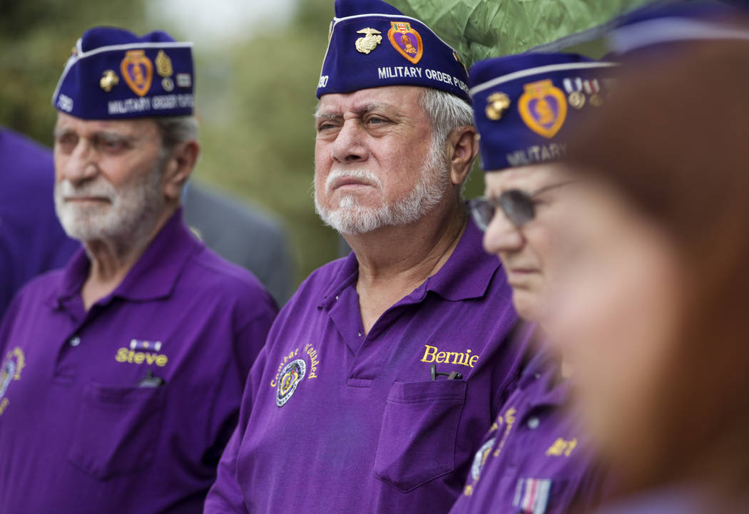 Bernie Santos, center, member of the Military Order of the Purple Heart Chapter 730, during the National Purple Heart Day memorial ceremony at the Southern Nevada Veterans Memorial Cemetery in Bou ...