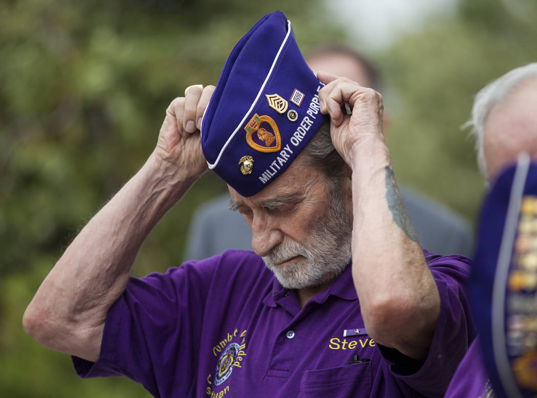 Steve Stevenson, left, trustee for the Military Order of the Purple Heart Chapter 730, during the National Purple Heart Day memorial ceremony at the Southern Nevada Veterans Memorial Cemetery in B ...