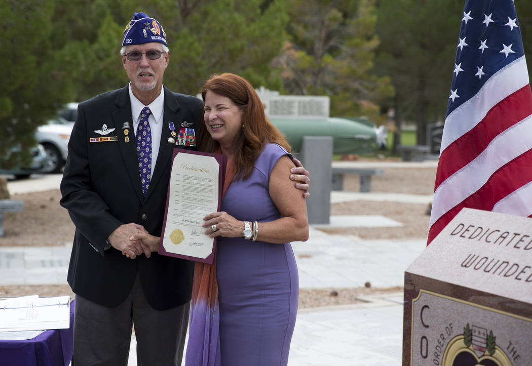 Henderson Mayor Debra March, right, presents a proclamation to Dan Peterson, commander of the Military Order of the Purple Heart Chapter 730, during the National Purple Heart Day memorial ceremony ...