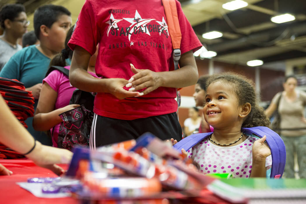 Yamuna Da Silva, 4, collects school supplies during the Back-to-School Fair hosted by Marianaճ Supermarkets at Clark High School in Las Vegas, Thursday, Aug. 3, 2017.  People waited outside  ...