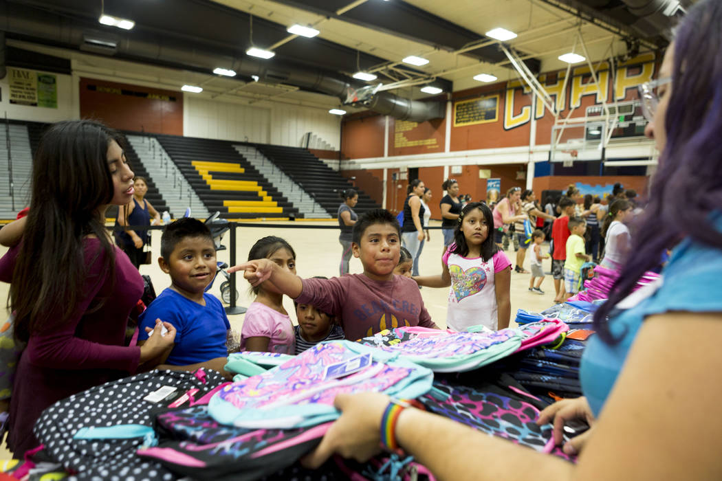 Students choose their new backpacks during the Back-to-School Fair hosted by Marianaճ Supermarkets at Clark High School in Las Vegas, Thursday, Aug. 3, 2017.  People waited outside for over  ...