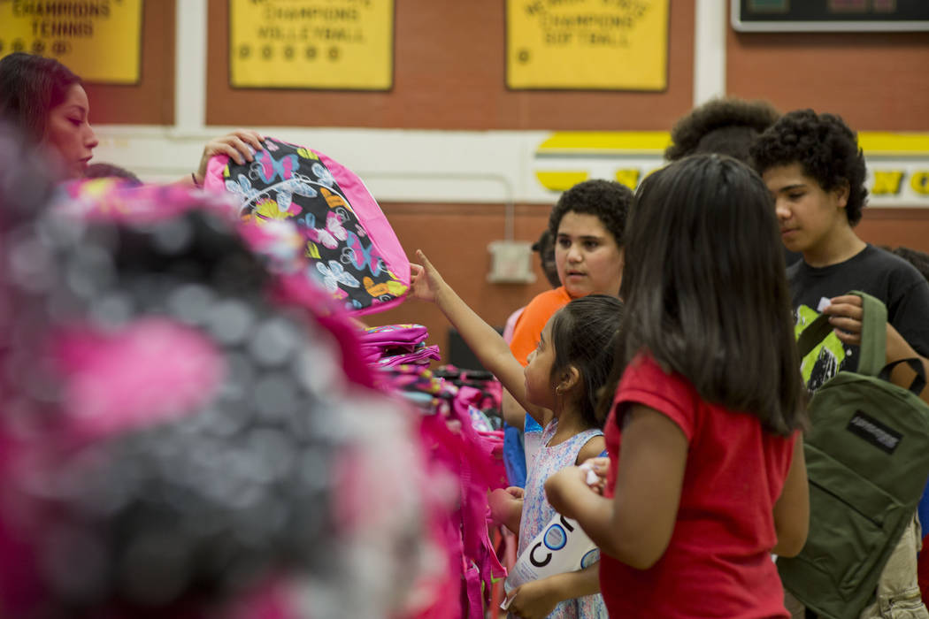 Students choose their backpacks during the Back-to-School Fair hosted by Marianaճ Supermarkets at Clark High School in Las Vegas, Thursday, Aug. 3, 2017.  People waited outside for over an h ...