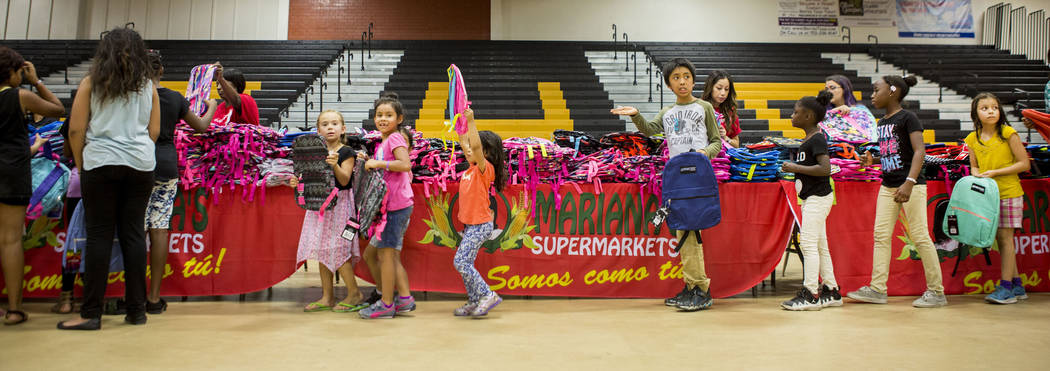 Students choose their backpacks during the Back-to-School Fair hosted by Mariana's Supermarkets at Clark High School in Las Vegas, Thursday, Aug. 3, 2017.  People waited outside for over an ...