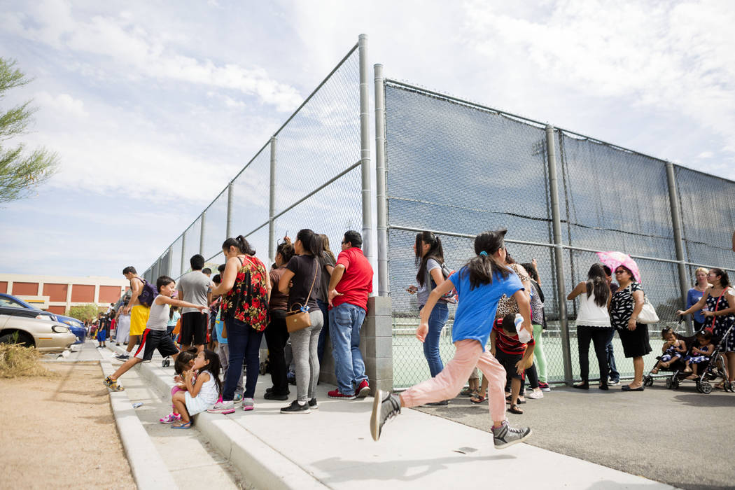 Families wait in line for over an hour to participate in the Back-to-School Fair  hosted by Marianaճ Supermarkets at Clark High School in Las Vegas, Thursday, Aug. 3, 2017.  General manager  ...